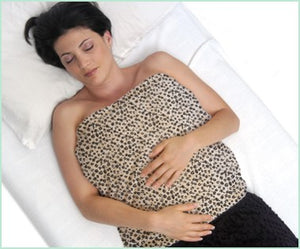 Weighted warming blanket covering front torso of a woman - leopard print fur velour - top view