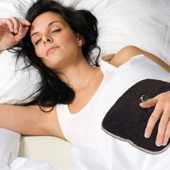 "Woman lying down with small square heating pad 9""x9"" on stomach - chocolate brown swirl velour"