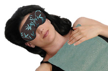 Woman wearing sleep mask with aqua blue silk with shimmering gold bamboo leaf pattern embroidery fabric.