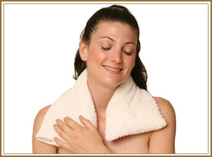 Woman with white spa wrap heating pad around neck & shoulders