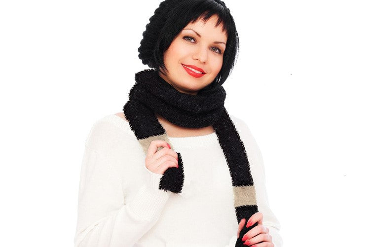 Woman wearing long black fur with white trim scarf around neck