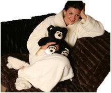 Woman in creamy white robe on brown sofa holding large black & white therapeutic teddy bear