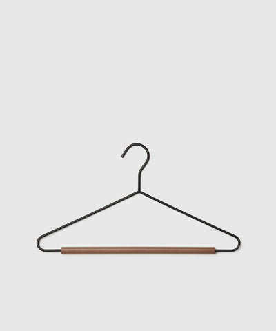 Matte black and beechwood pant and suit hanger. The Serene Closet Collection for The Container Store x KonMari joyfully designed by Marie Kondo.
