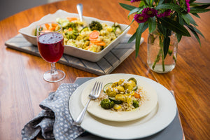 A plate and casserole dish full of flavor, and richness using coconut milk, and brown rice topped with a variety of vegetables, and chicken all seasoned with curry.  Paired with a glass of blueberry kombucha.