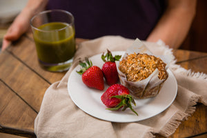 Fresh banana coconut muffin with side of strawberries and Sweet green juice.