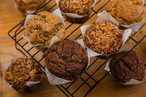 An arrangement of gluten free muffins, including apple pie, banana coconut, and peanut butter dark chocolate chip.