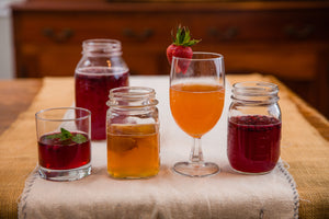 Glasses of a variety of kombucha flavors including fig, cinnamon apple vanilla, blue berry mint, and blueberry lavender.