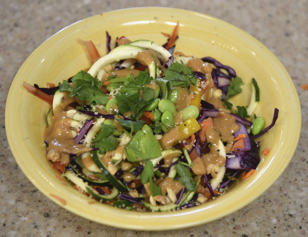 A bowl full of healthy, raw veggies, with a house made spicy, peanut sauce.  Vegetables include spiralized zucchini, shredded carrots, sliced peppers, cabbage, edamame, and onions, sprinkled with sesame seeds, peanuts, and cilantro.