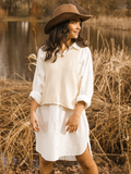 Model wearing oversized white shirt dress underneath cream coloured sweater vest
