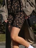 Close up shot of model wearing tan coloured leopard printed bike shorts with green trench coat