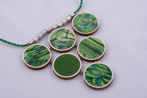 Green statement necklace made with fabric on light wood base