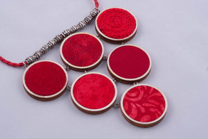 Red statement necklace made with fabric on light wood base
