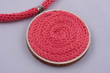 Statement necklace made with colorful yarn on light wood base