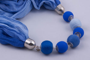 Blue scarf decorated with beads and beads covered by yarn (shades of blue)