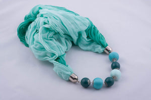 Turquoise scarf decorated with beads and beads covered by yarn (shades of turquoise)