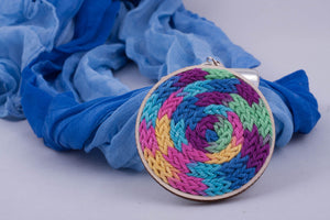 Blue scarf with pendant made with multi-color yarn on light wood base