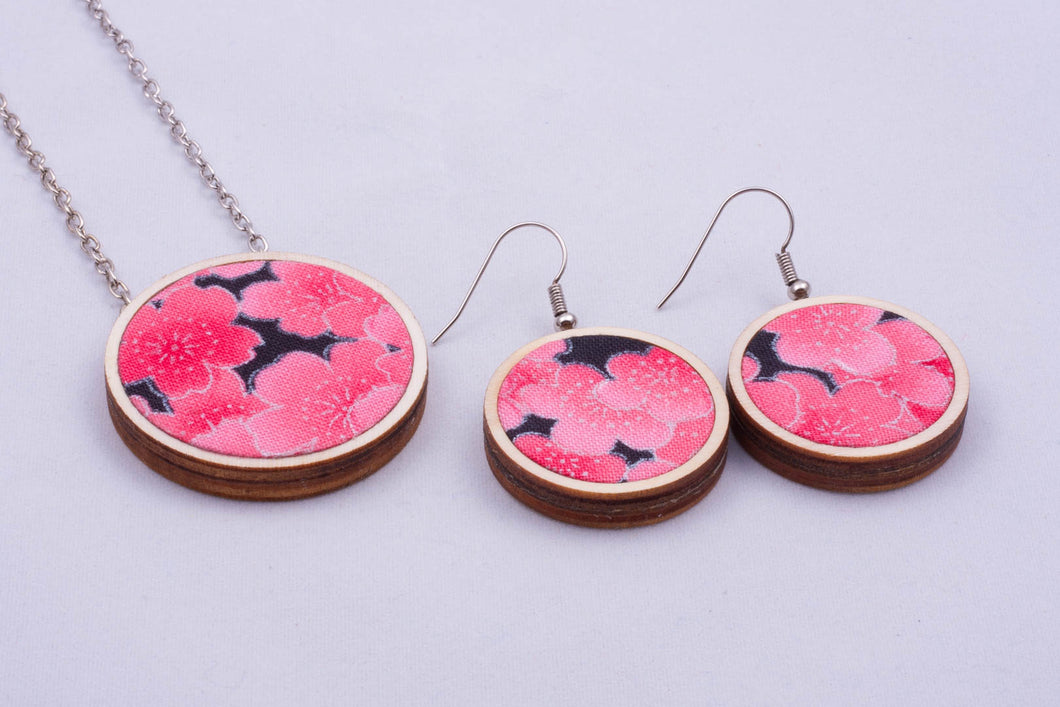 Necklace and matching earrings made with colorful fabric on light wood base