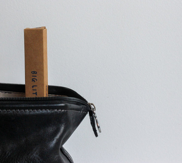 cute leather bag with big little brush poking out the top