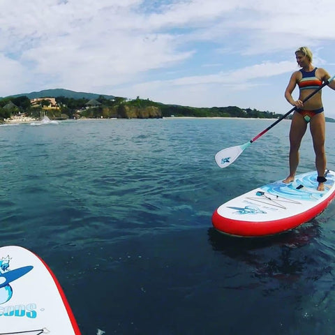 Female standing on a SUP board