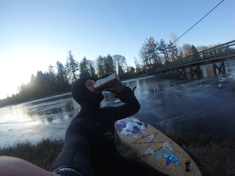 A paddle boarder in a wet suit drinking coffee from a thermos