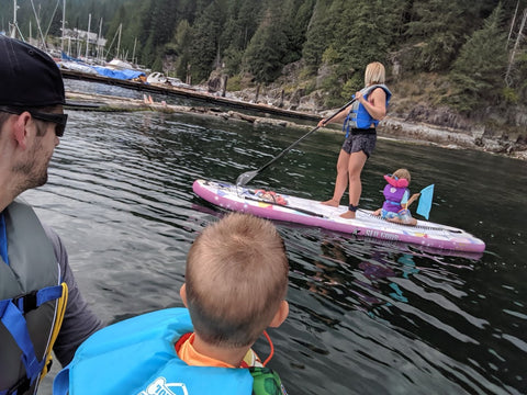Adults and kids wearing life jackets on paddleboards.