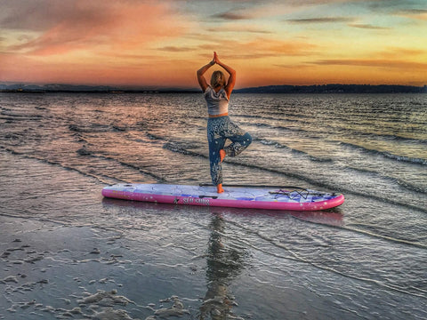 A woman in a yoga pose on the Infinite Manta board at sun rise.
