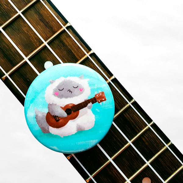 Ukulele Cat - Button or magnet with a digital painting of a cat playing the ukulele and singing.