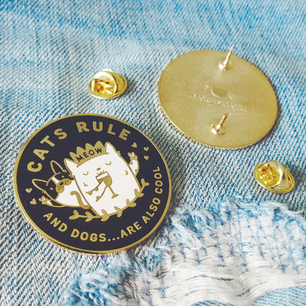 Cats Rule And Dogs Are Also Cool - Gold plated enamel pin with an illustration of a cat wearing a crown and drinking wine in front of a dog by My Cat Is People.