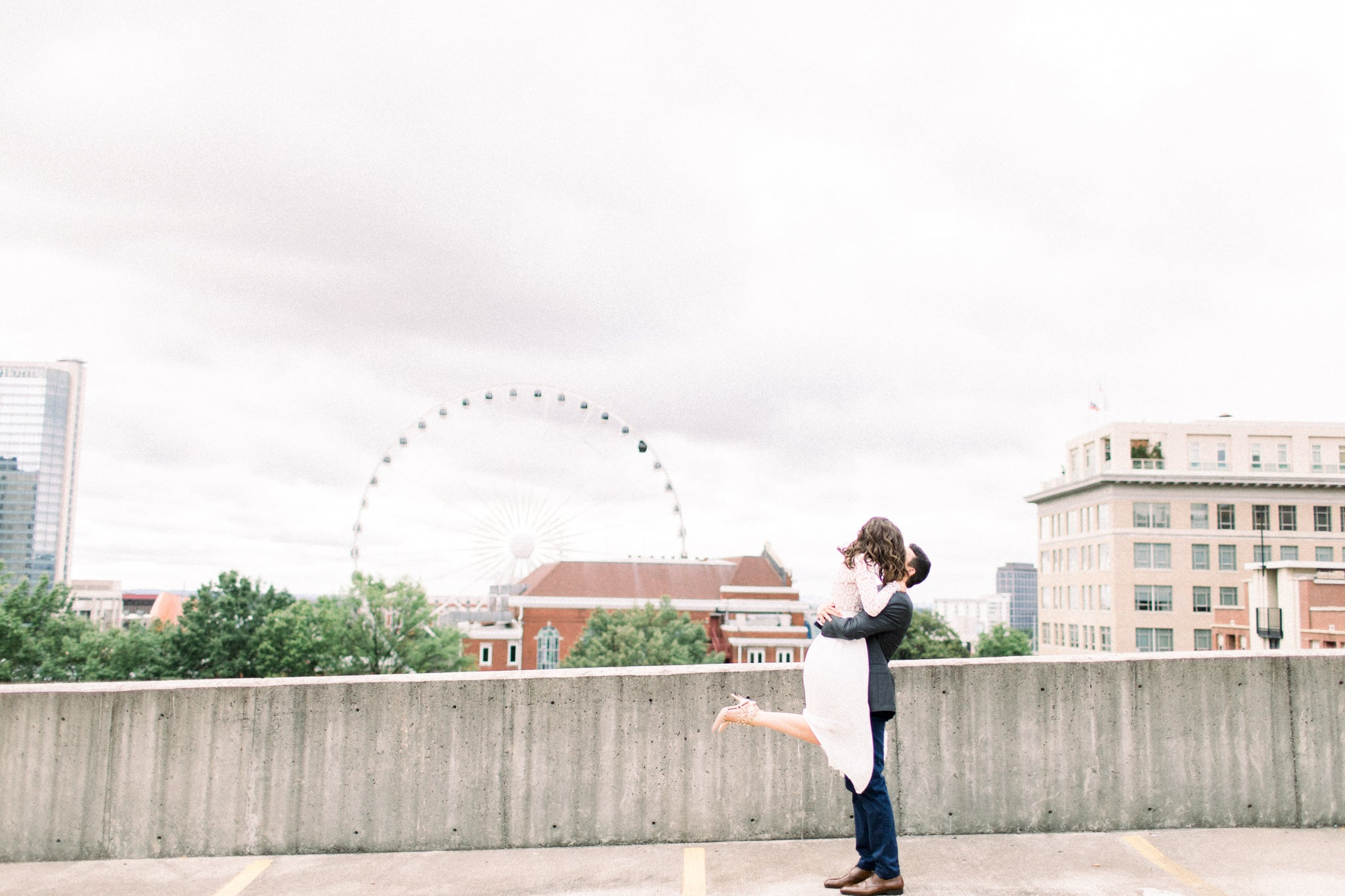fiancé lifting his bride to be wearing her little white dress taking engagement photographs