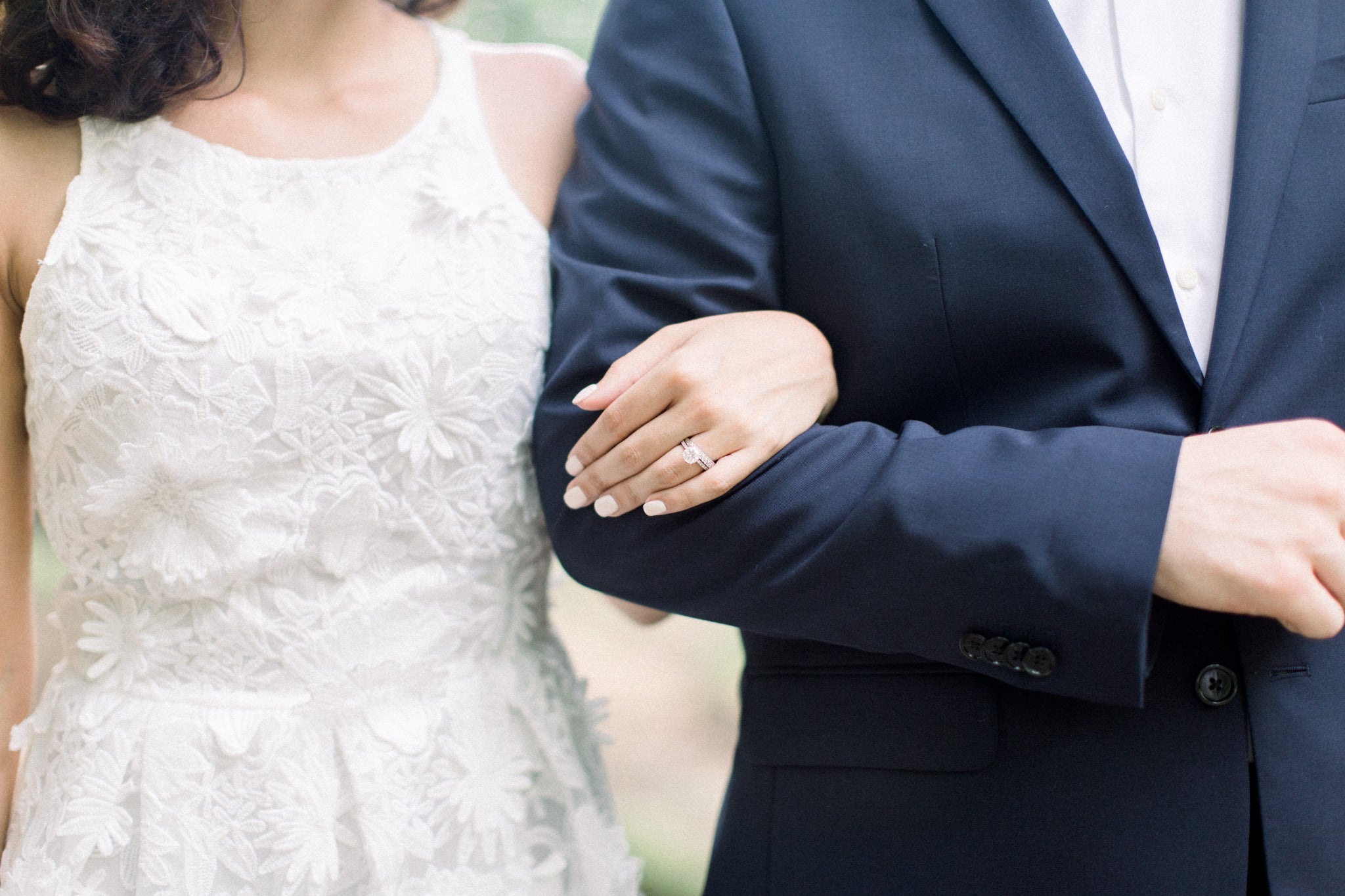 bride to be in little white dress locking arms with her fiancé featuring her engagement ring