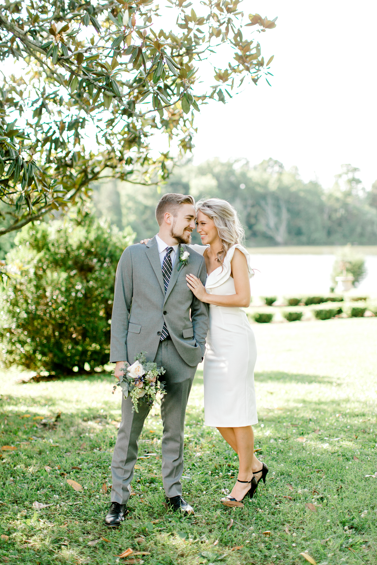 bride wearing little white dress smiling with her fiancé taking engagement photographs