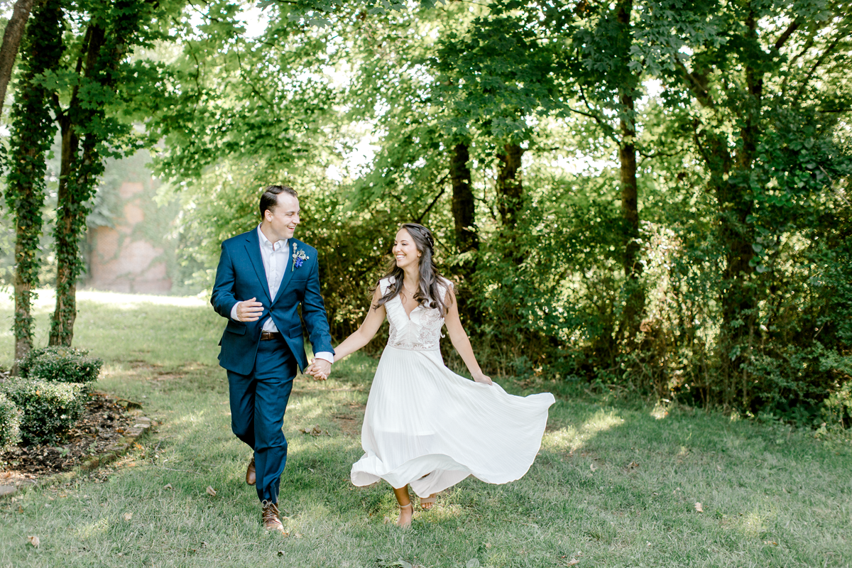 excited bride in flowy white dress taking engagement photos with her fiancé