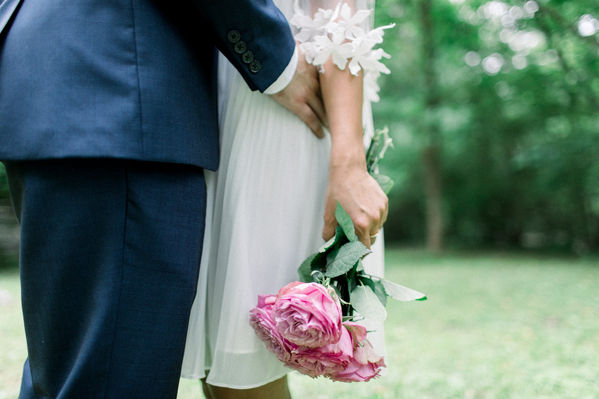 bride in little white dress holding flowers with her fiancé taking engagement photographs