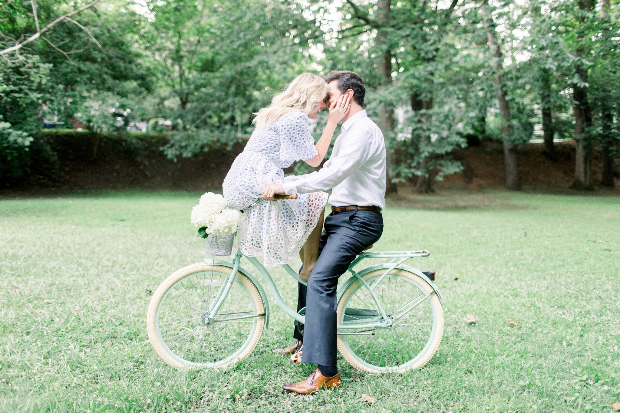 excited bride in long white dress with her fiancé riding bikes in the park smiling at one another