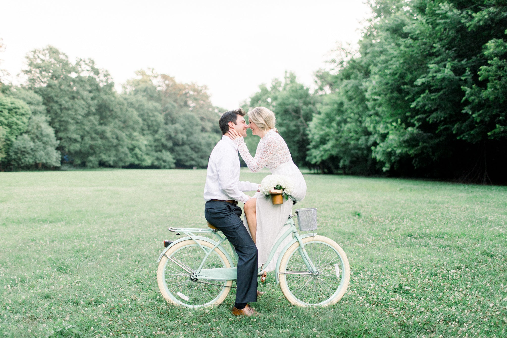 bride sitting on bike wearing little white dress with her fiancé taking engagement photographs