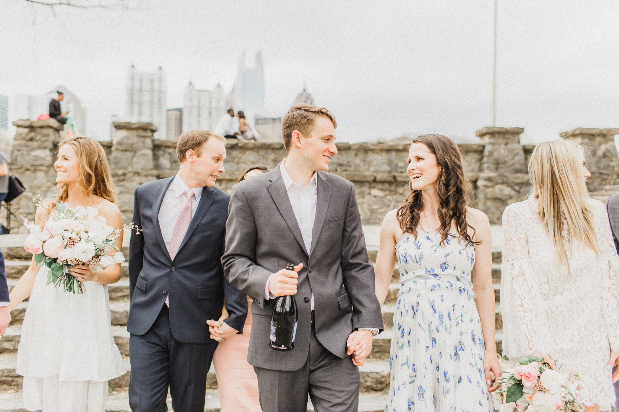 smiling groom with his bride to be and wedding party holding a bottle of Le Marca Champagne