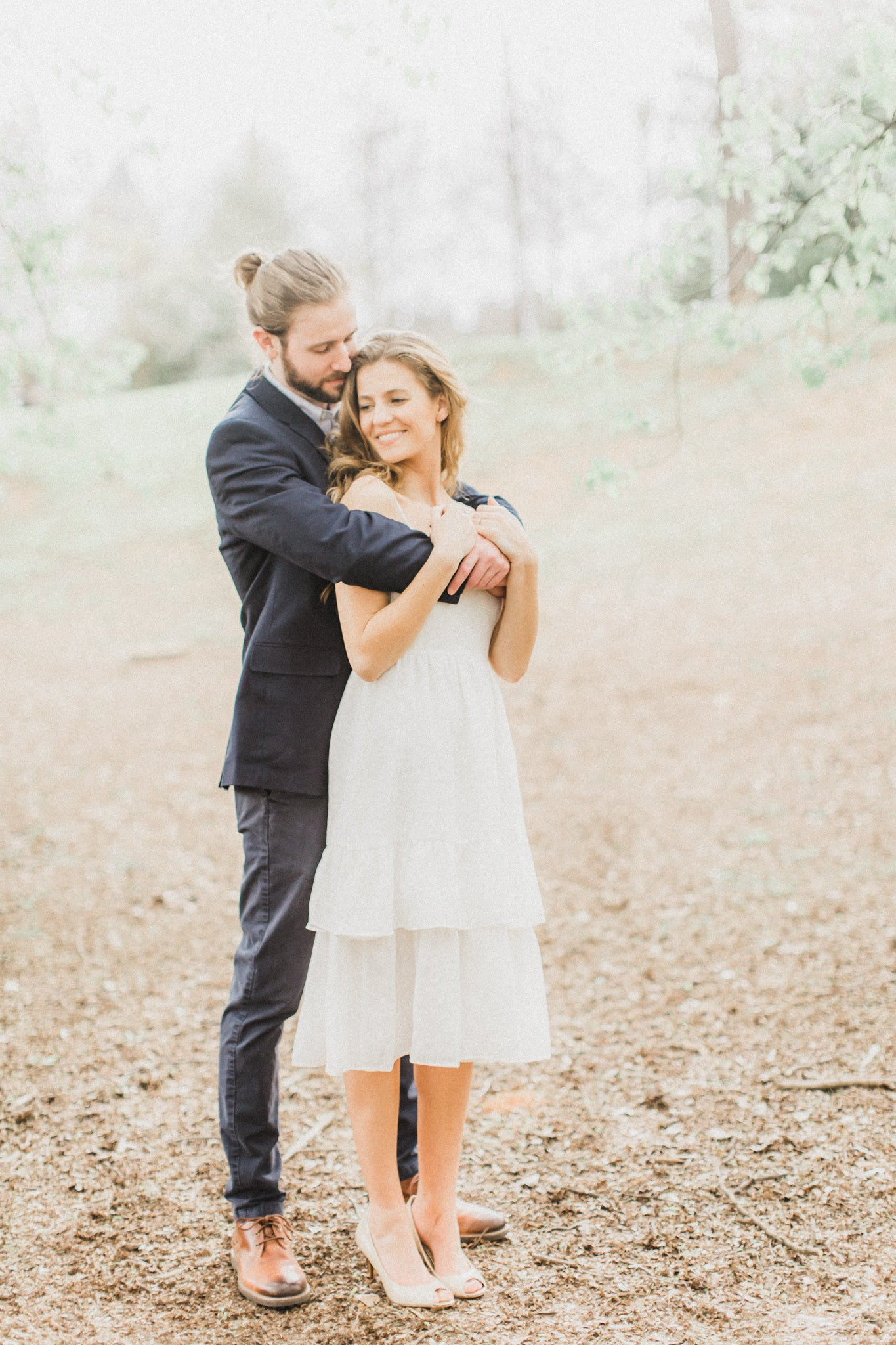 bride to be in mid length little white dress taking engagement photos with her fiancé outside