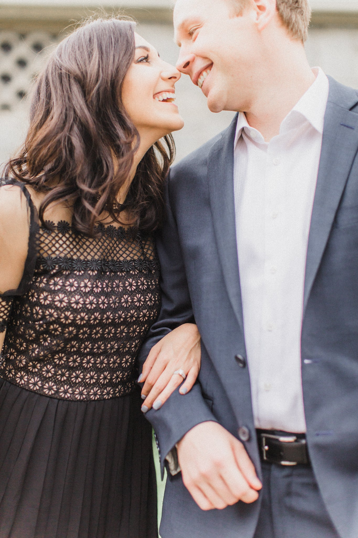 happy bride taking engagement photos with her fiancé featuring her engagement ring