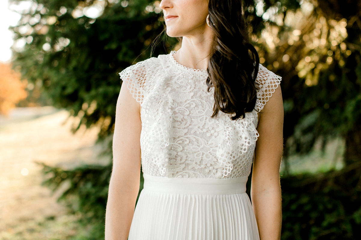 bride to be in little white dress wearing a pair of gold dainty bridal earrings