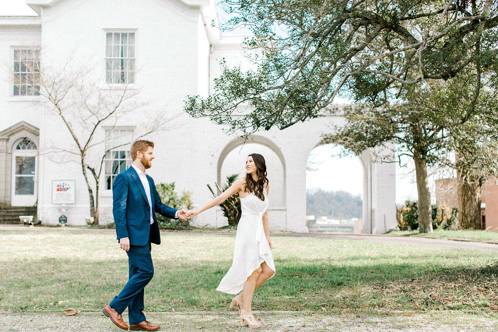 bride in little white dress holding onto her fiancés hand taking their engagement photographs