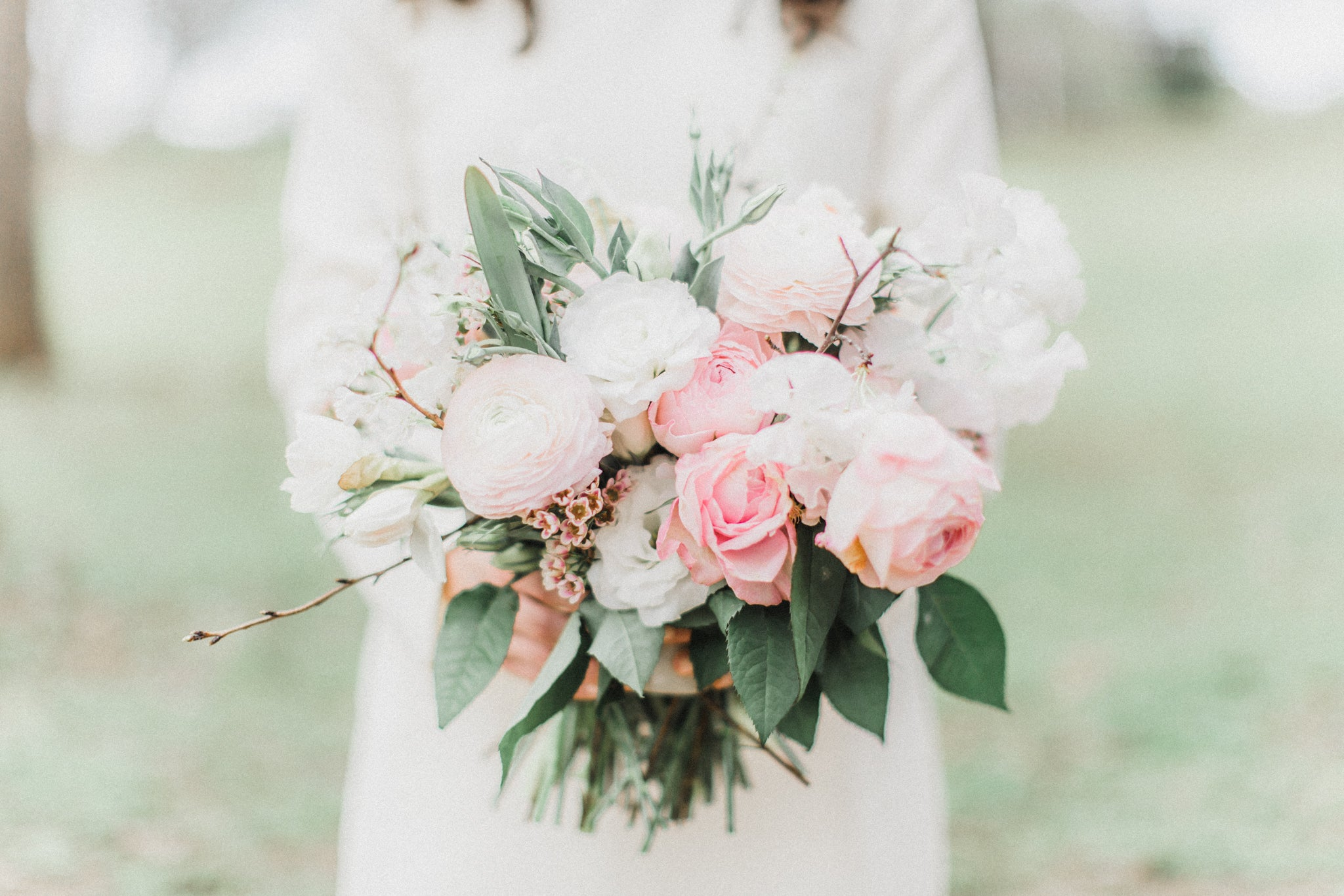 bride in little white dress holding flower bouquet for engagement photos