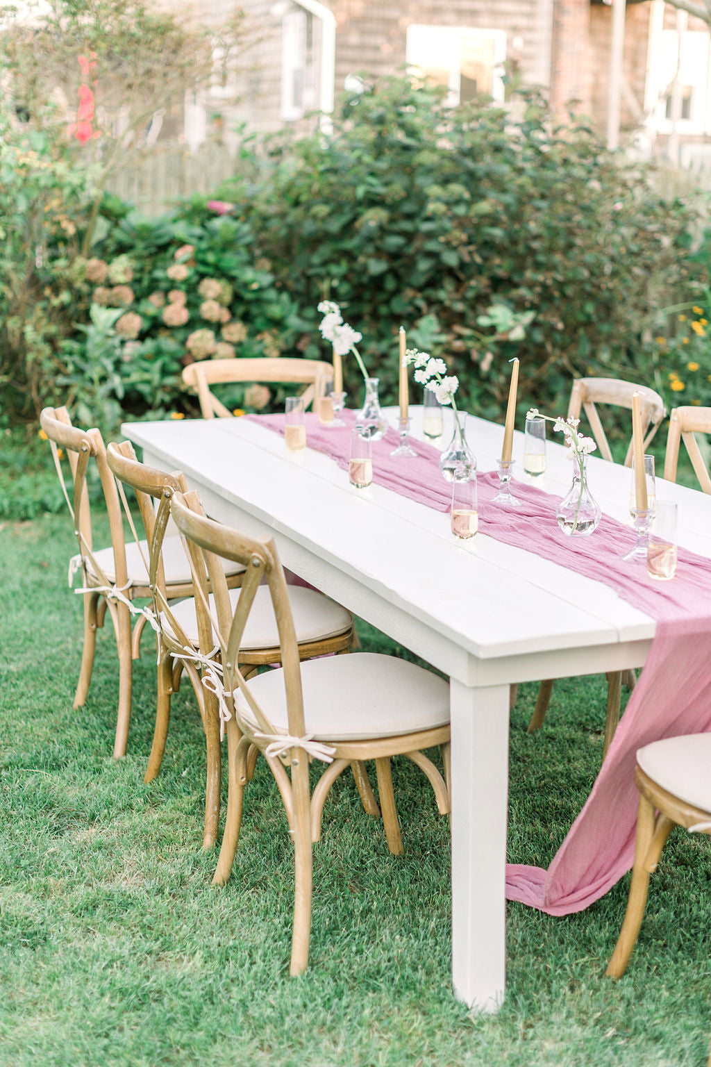 Wedding reception table with pink table runner, candles, and champagne flutes