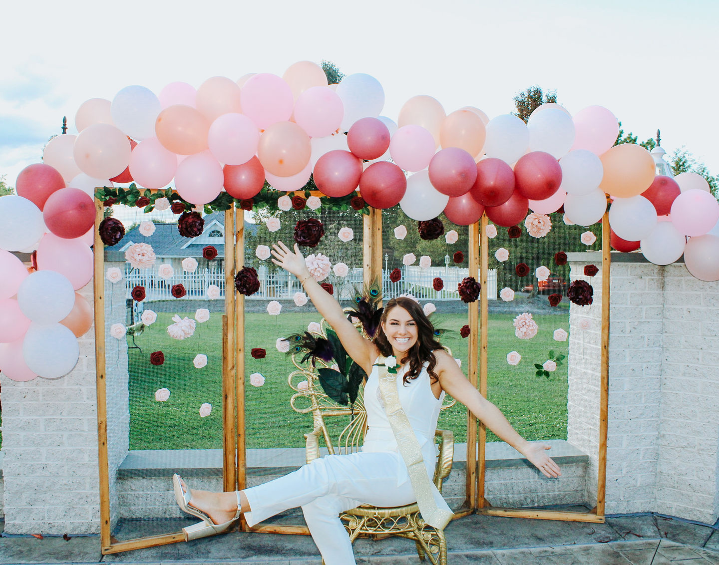 Bride celebrating at her bachelorette party in a white bridal jumpsuit