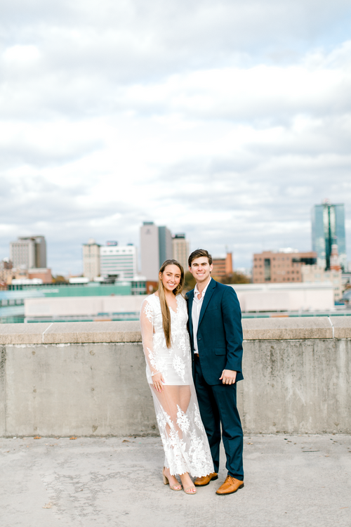 Couple posing for engagement photos in front of Knoxville, TN downtown skyline | The Olivia | Eternal Ivory