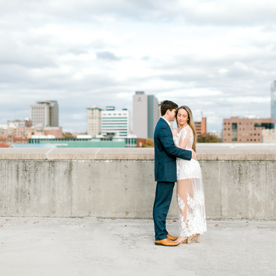 Couple embracing during engagement photos in front of Knoxville, TN downtown skyline | The Olivia | Eternal Ivory