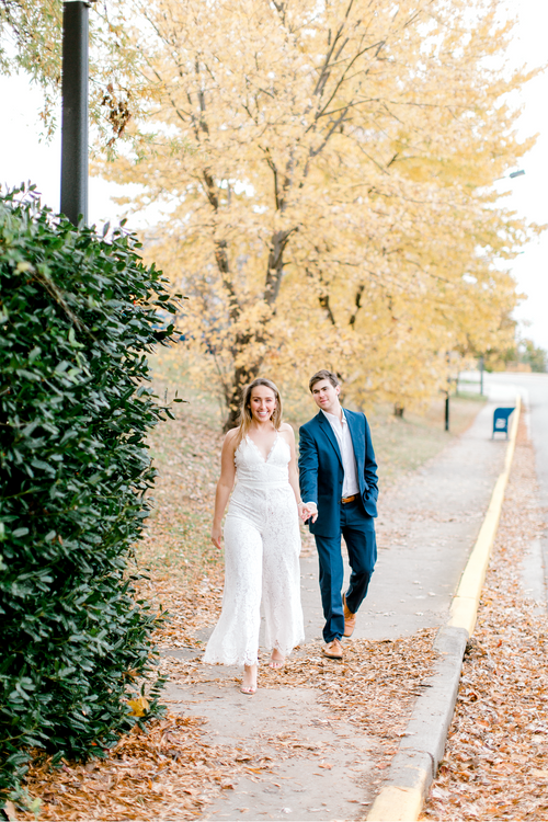 Engaged couple strolling through their engagement photo session | Bride wearing lace jumpsuit | The Blakely | Eternal Ivory
