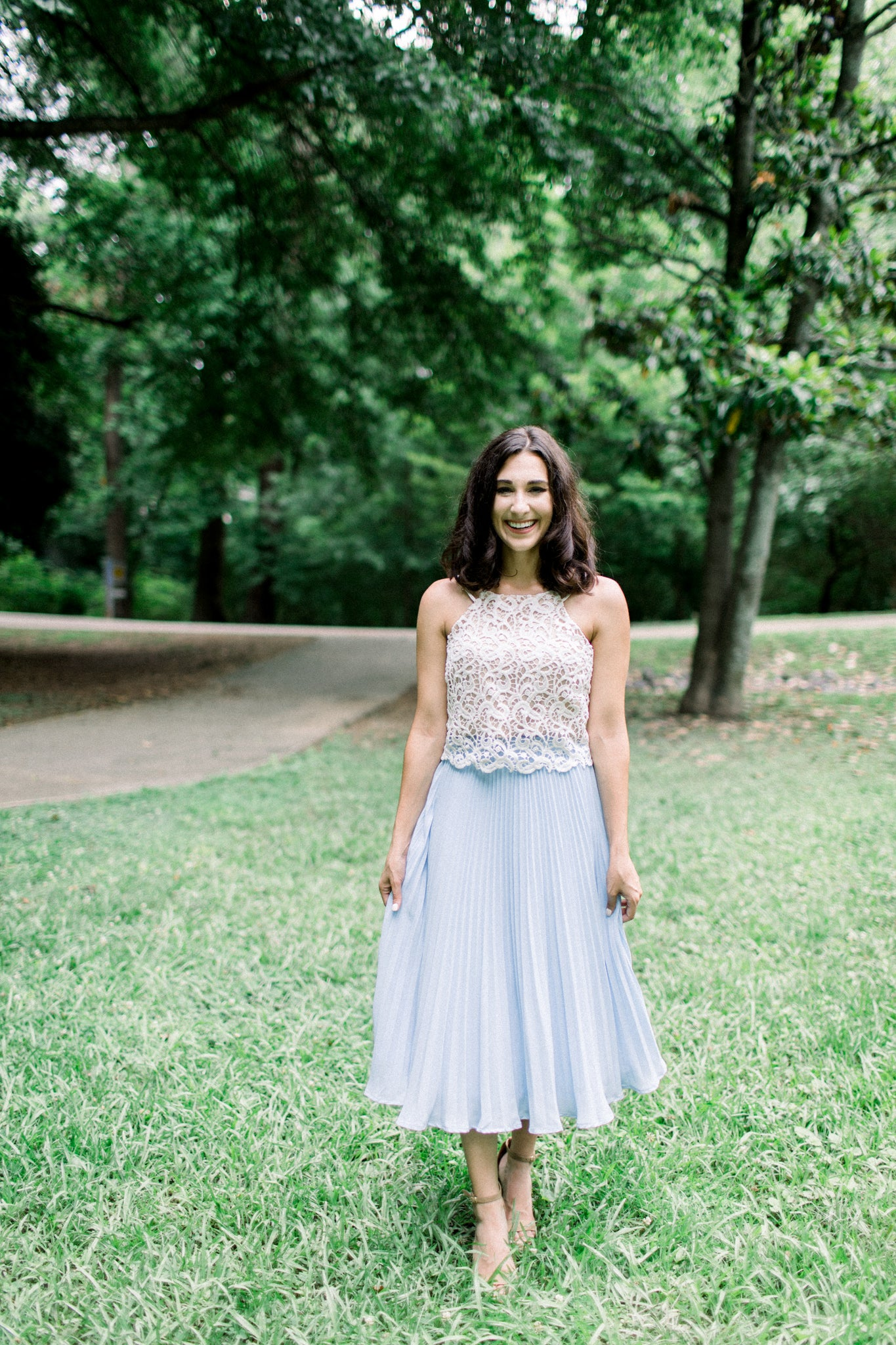c838b6fa4b0 A beautiful white lace top combined with a high-waisted pleated midi skirt  is a great alternative to the traditional dress option.