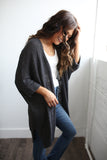 3/4 Rolled sleeve ribbed knit open front cardigan sweater with side slits. Charcoal. Available in sizes S,M,L,XL,1X, and 2x.
