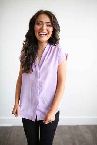 This gorgeous woven top is perfect for work or play! Available in classic white, or a beautiful bright lavender color. Split back detail offers a great fit.