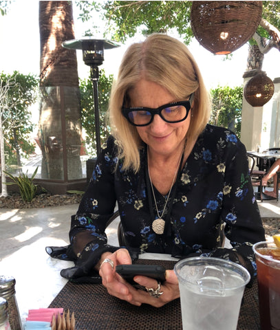 A blonde woman (Ann) wearing reading glasses and looking at her phone.  She is wearing Blue Agnes jewelry, specifically the silver medallion lace Elizabeth Necklace, the silver scuptural Natalie Ring, and three silver Thumbpring Rings stacked on her right index finger. She is smiling softly and looks happy.